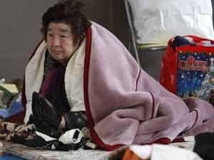 Idosa tenta se proteger do frio no Japão (Foto: AP)