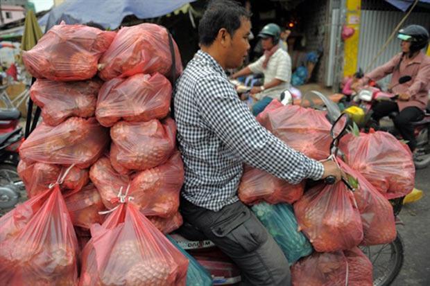 Cambojano foi flagrado com moto carregada de abacaxis em Phnom Penh. (Foto: Tang Chhin Sothy/AFP)