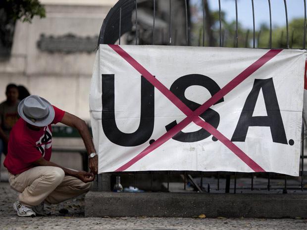 Homem coloca cartaz anti-americano na Cinelândia, centro do Rio, onde Obama fará discurso no domingo (20) (Foto: Felipe Dana / AP)