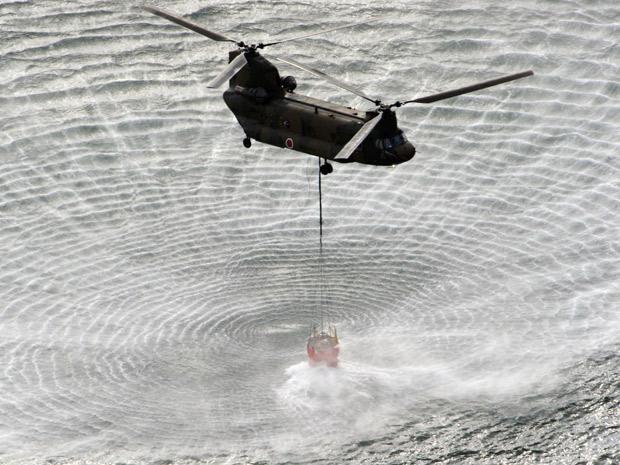 Helicóptero retira água do mar para jogar em usina de Fukushima (Foto: Reuters)