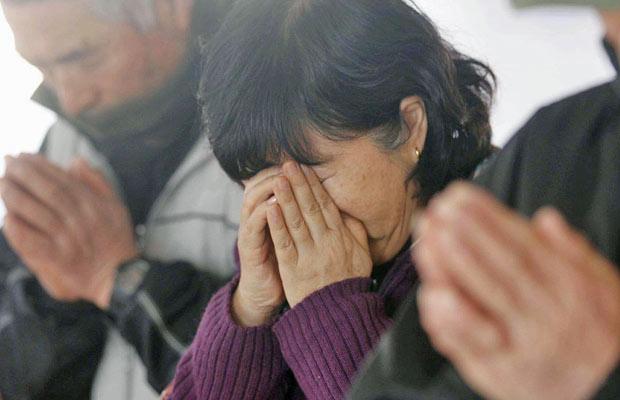 Moradores fazem um minuto de silêncio em Ofunato, na província de Iwate, nesta sexta (Foto: AP)
