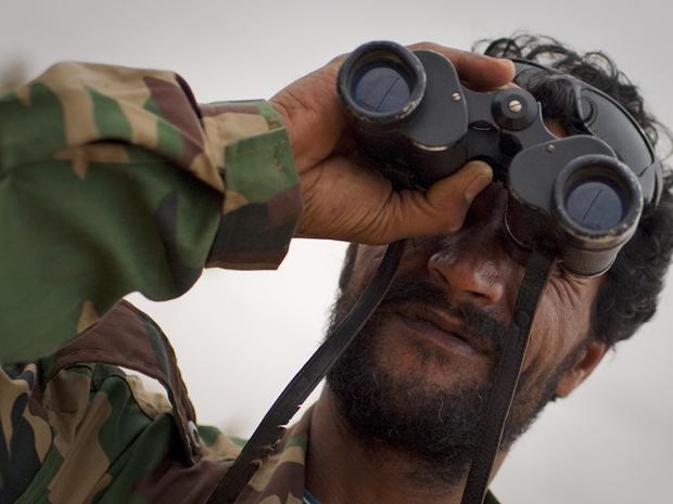 Rebelde tenta avistar aviões próximo à cidade líbia de Benghazi nesta sexta-feira (18) (Foto: AP)