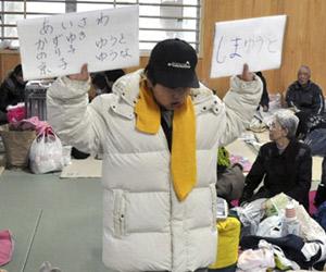 Menino japonês percorre abrigos com placas com nomes dos pais (Kuniaki Nishio/AP)