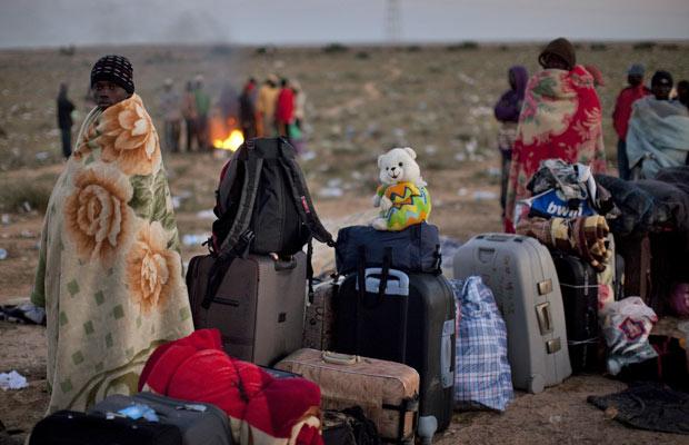 Refugiados esperam para serem repatriados na fronteira da Líbia com a Tunísia. Mais de 250 mil pessoas já deixaram a Líbia desde fevereiro (Foto: Emilio Morenatti/AP)