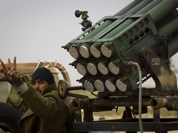 Rebelde líbio faz sinal de vitória ao chegar à fronteira de Benghazi (Foto: AP)