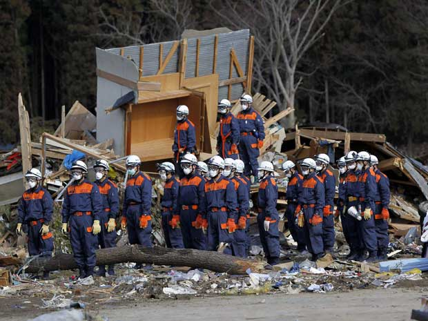 Equipe de resgate observa um minuto de silêncio em Rikuzentakata, em Iwate. (Foto: Aly Song / Reuters)
