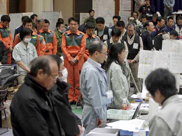 Funcionários da prefeitura de Miyagi, em Sendai, no norte do Japão, param e oram durante um minuto, em homenagem às vítimas dos desastres naturais que completarm uma semana. (Foto: Yomiuri Shimbun / Hirofumi Nagao / AP Photo)