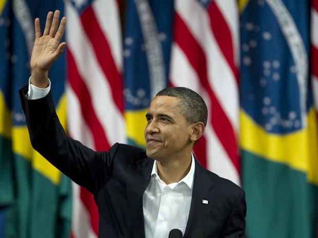 Presidente dos EUA dispensou a gravata neste domingo (20); na foto ele acena antes de discursar no Teatro Municipal do Rio (Foto: Victor R. Caivano/AP)