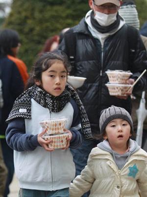 Família evacuada da cidade de Miyagi recebe arroz e carne saudáveis para comer. (Foto: Jiji Press / AFP Photo)