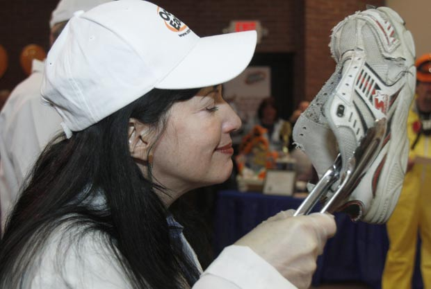 Juíza Rachel Herz cheira tênis durante o Concurso Nacional de Desodorantes para Tênis Fedorentos. (Foto: Toby Talbot/AP)