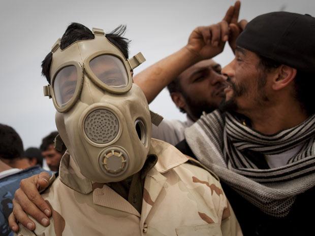 Rebelde comemora com máscara de gás na Líbia (Foto: Anja Niedringhaus/AP)