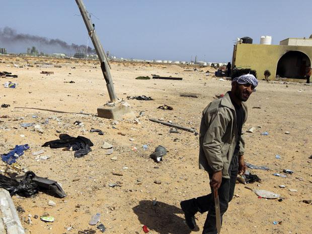Rebelde caminha perto de terminal de petróleo em Ras Lanuf, na Líbia (Foto: Youssef Boudlal/Reuters)