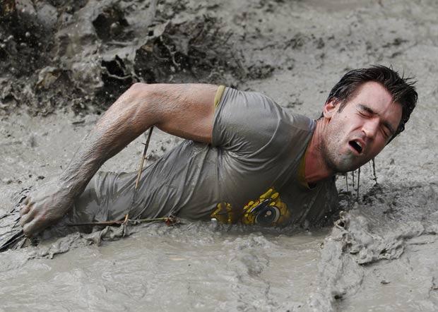 Participante nada na lama durante a prova desgastante. (Foto: Pascal Lauener/Reuters)