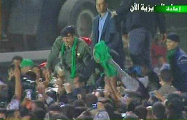 Imagem da TV estatal líbia mostra Khamis (esquerda) cumprimentando apoiadores em local próximo à sua residência em Trípoli (Foto: AFP)