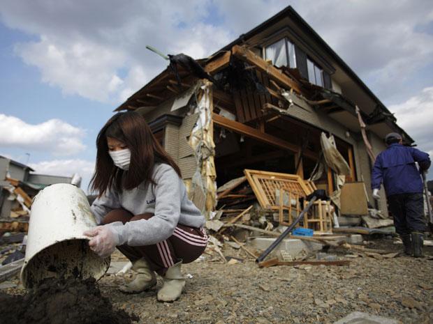 Japonesa tenta limpar a sujeira que invadiu sua casa, atingida pelo tsunami em Miyagi. (Foto: Carlos Barria / Reuters)