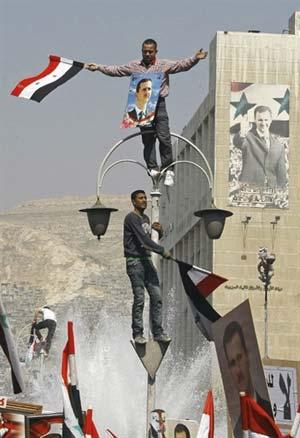 Manifestantes empunham bandeiras e fotos do presidente Bashar al-Assad em manifestação de apoio nesta terça (29), em Damasco (Foto: Anwar Amro / AFP)