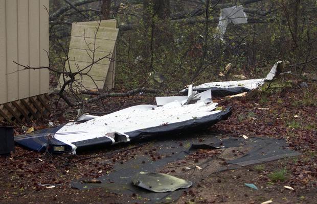 Destroços de pequeno avião que caiu nesta quarta-feira (30) sobre casa em High Point, no estado americano da Carolina do Norte. A aeronave caiu e provocou um incêndio na residência, segundo as autoridades e vizinhos. As duas pessoas a bordo morreram, mas os moradores escaparam ilesos. (Foto: AP)