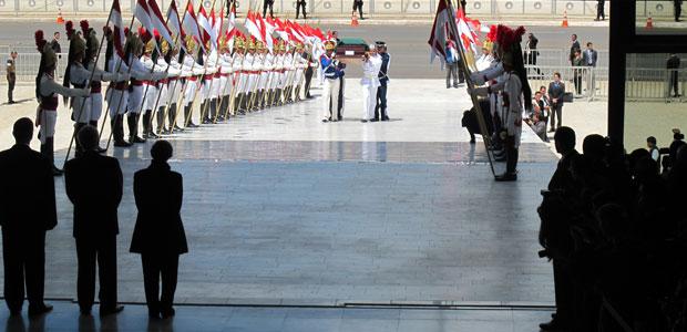 De costas, a viúva de Alencar e o presidente em exercício Michel Temer aguardam a chegada do caixão pela rampa do Palácio do Planalto  (Foto: G1)