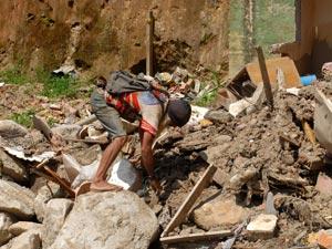 Homem garimpa material entre os escombros para depois revender (Foto: Alexandre Durão/G1)