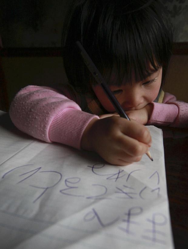 """Usando caracteres """"hiragana"""" que acabou de aprender, a menina Manami Kon escreve carta para a mãe ainda desaparecida após a tragédia de 11 de março no Japão; """"Querida mãe. Eupero que você esteja viva. Você está bem?"""", diz mensagem. (Foto: Yomiuri Shimbun, Norikazu Tateishi / AP)"""