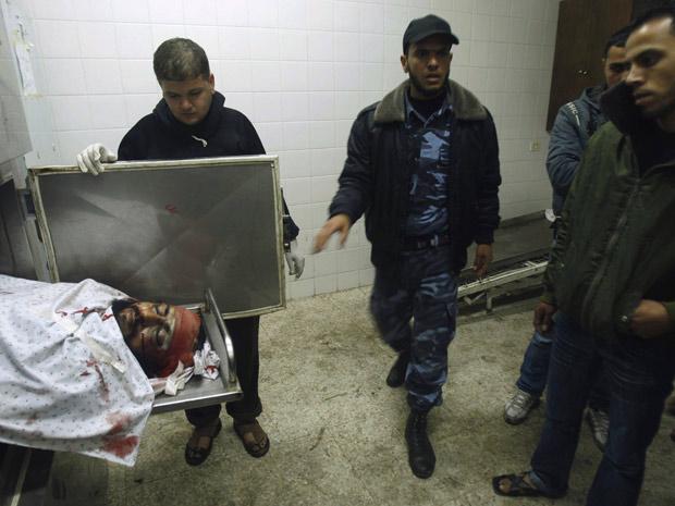 Membros do Hamas observam corpo de militante morto após ataque aéreo israelense em Deir Al-Balah, na Faixa de Gaza (Foto: Ibraheem Abu Mustafa / Reuters)
