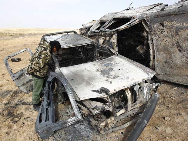 Rebelde líbio observa carro queimado por ataque aéreo da coalizão que deixou dez mortos entre Ajdabiyah e Brega (Foto: Andrew Winning / Reuters)