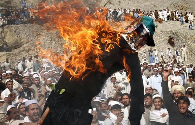 Boneco representando o pastor norte-americano Terry Jones é  queimado nesta segunda-feira (4) durante protesto em Shinwar,na  província afegã de Nangarhar. O religioso da Flórida foi novamente alvo  de protestos, após ele ter queimado, em 20 de março, um exe (Foto: AP)