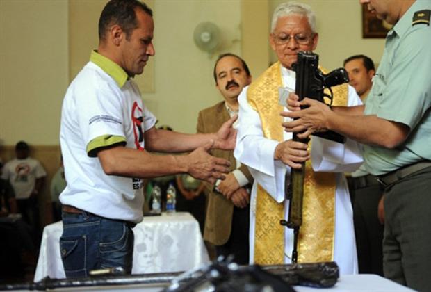 Membro de quadrilha de favela de Medellín, na Colômbia, entrega armas para padre durante cerimônia em igreja nesta segunda-feira (4). Cerca de 80 integrantes de gangues depuseram suas armas e prometeram parar com a violência. (Foto: AFP)