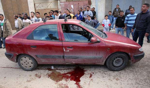 Moradores observam carro em que o ator e diretor foi assassinado, em frente ao Teatro Liberdade, em Jenin, nesta segunda (4) (Foto: Mohammed Ballas / AP)