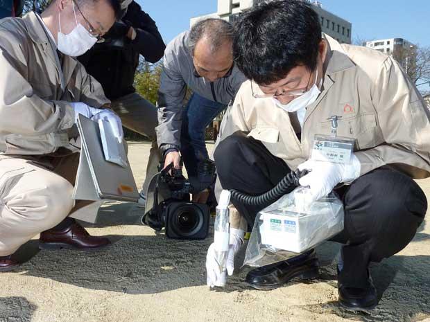 Funcionários públicos medem radiação em uma escola primária  em Fukushima. (Foto: Kyodo News / AP Photo)