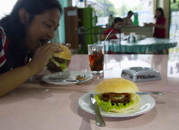 Cliente come hambúrguer com carne de cobra. (Foto: Dwi Oblo/Reuters)