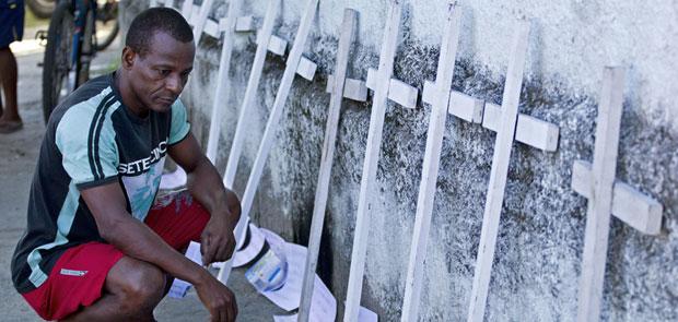 Cruzes de madeira colocada no muro da escola no Rio (Foto: AP)