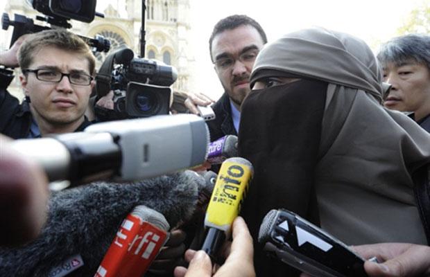 Kenza Drider fala com a imprensa em frente à catedral de Notre Dame, em um protesto contra a proibição do uso do véu islâmico integral que entra em vigor nesta segunda, na França (Foto: Bertrand Guay/AFP)