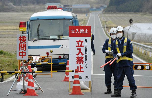 Policiais inspecionam homem em Minamisoma, a cerca de 20km da usina de Fukushima (Foto: AP)
