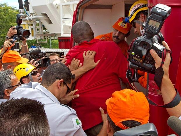 O homem que queimou a bandeira é conduzido a uma ambulância após ter sido preso por agentes da Polícia Federal (Foto: Dorivan Marinho/Futura Press)