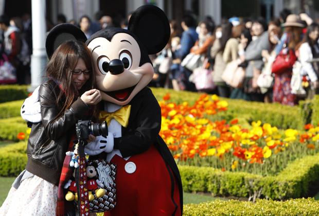 Japonesa abraça o camundongo Mickey nesta sexta-feira (15) na Disneylândia de Tóquio, em Urayasu, a leste da capital do Japão. (Foto: Reuters)