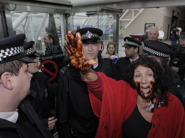 Coberta de óleo, a americana Diane Wilson, do Texas, protesta contra a BP durante reunião anual de acionistas da empresa petrolífera em Londres, nesta quinta (14)  (Foto: Lefteris Pitarakis / AP)