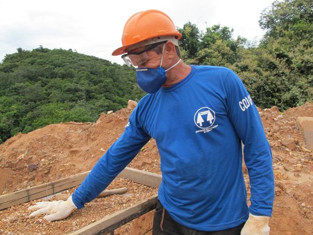 Depois de passar pela peneira, material é descartado e fica em montes como os que estão atrás do garimpeiro.  (Foto: Anay Cury/G1)