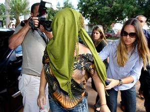 promotora de Justiça Deborah Guerner (coberta com um lenço) chega à sede da Polícia Civil de Brasília, nesta quarta-feira (20), após ter sido presa no Aeroporto Internacional Juscelino Kubitschek (Foto: CELSO JUNIOR/AGÊNCIA ESTADO/AE)