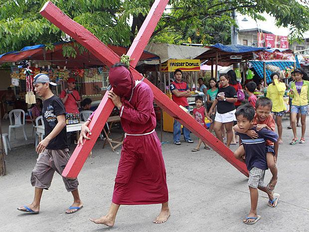 Homem carrega cruz para imitar o sofrimento de Jesus Cristo (Foto: Erik de Castro/Reuters)