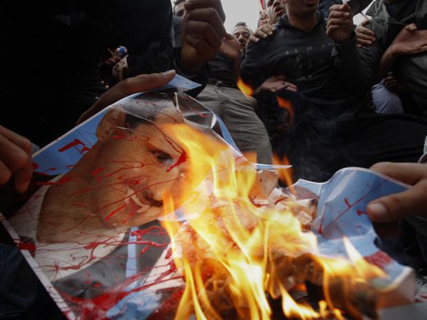 Manifestantes queimam foto do presidente da Síria, Bashar al Assad, durante protesto nesta sexta-feira (22) em Nicósia, capital de Chipre (Foto: AP)