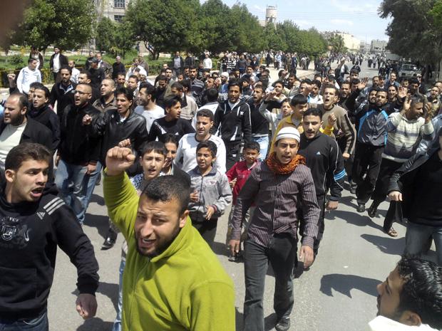 Manifestantes protestam na cidade síria de Homs nesta sexta-feira (22) (Foto: AP)
