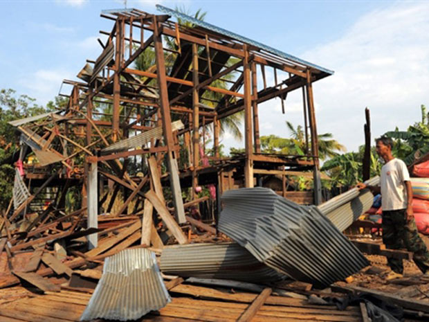 Homem olha para casa destruída por ataque tailandês no Camboja (Foto: Tang Chhin Sothy/AFP)