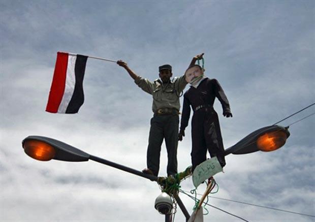 Manifestante pede saída de Saleh do poder com boneco com foto do rosto do presidente, neste sábado (23), na capital o Iêmen. (Foto: AFP)