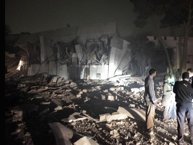 Pessoa conversam próximo um prédio do complexo Bab al-Aziziya, de Muammar Kadhafi (Foto: Louafi Larbi/AFP)