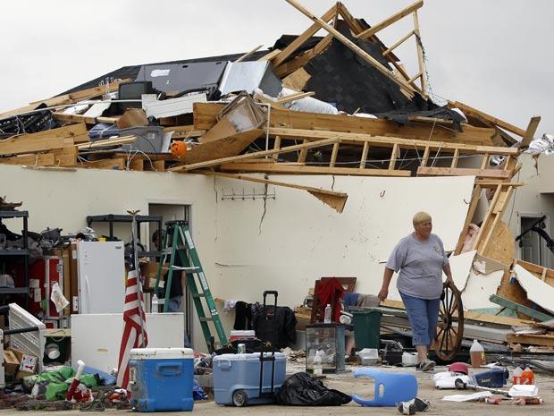 Moradora tenta recuperar objetos em casa destruída por tornado nos Estados Unidos (Foto: AP)