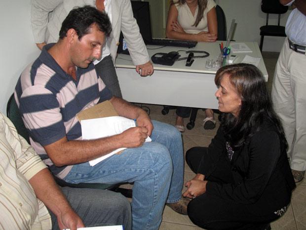 Rodrigo Santos assina a ata das reivindicações feitas pelos agricultores, observado por Conceição Ribeiro. (Foto: Bernardo Tabak/G1)