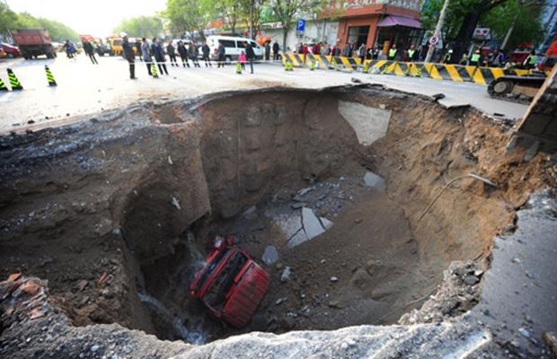Equipes cercam buraco de rua em Shiliuzhuang, em Pequim, na terça-feira (26). O buraco abriu-se sob um caminhão, que caiu, ferindo levemente o motorista e um passageiro, que conseguiram saltar antes da queda. As autoridades suspeitam que o buraco tenha sido provocado pelas obras de uma linha de metrô. (Foto: AFP)