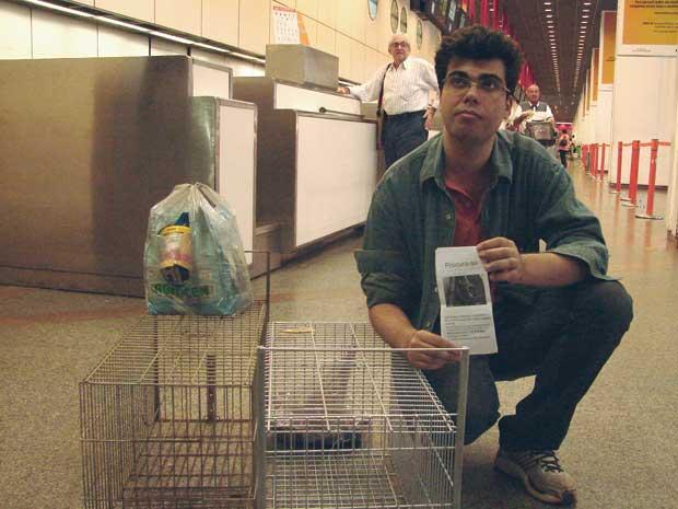 O pesquisador Maicon Saul Faria, que perdeu o gato de estimação na última segunda-feira no aeroporto internacional de Brasília, com a armadilha usada para tentar recuperar o animal (Foto: G1)