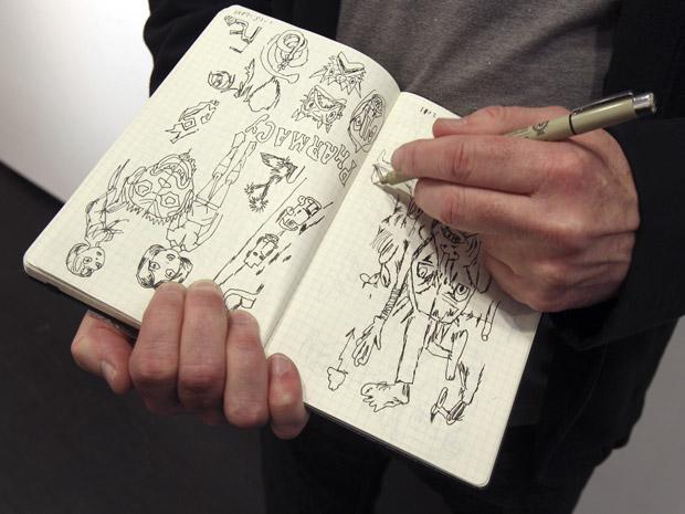 Em Paris para a inauguração da exposição, Gary Panter revela seu caderno de anotações. Além do trabalho com quadrinhos e pintura, Panter também ilustrou capas de discos do Red Hot Chili Peppers e da banda The Germs. A exposição fica em cartaz em Paris até 4 de junho. (Foto: Michel Euler/AP)